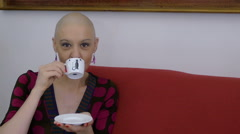 young woman with cancer relaxing and having coffee on the sofa at home - stock footage