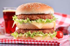Appetizing double cheeseburger and glass of soda Stock Photos