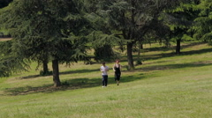 A man and woman jogging in the park Stock Footage