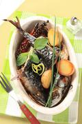 Oven baked mackerel and halved new potatoes in a casserole dish Stock Photos