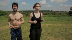 A man and a woman keep in fit  running in a park, jogging, steadicam shot Stock Footage