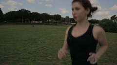 Young woman jogging in the park, steadycam shot Stock Footage