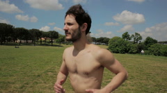 Young man makes sport running in a park Stock Footage