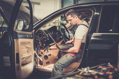 Serviceman making car diagnostics with laptop in a workshop Stock Photos