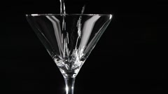 Martini being poured into a glass on black background. Slow motion. Stock Footage