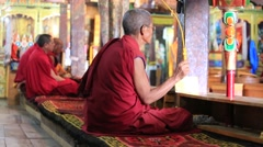 Buddhist monks singing prayers in traditional dress in Tiksey Monastery, India Stock Footage