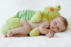 Little baby boy, sleeping with frog toy Stock Photos