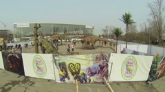 People with children walk by Dino-Park with artificial dinosaurs Stock Footage