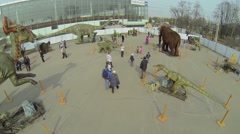 Parents and children walk by Dino-Park with artificial dinosaurs Stock Footage