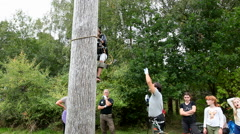 Instructions are given to a person Spar Pole Climbing for the first time Stock Footage