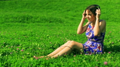 Romantic girl wearing headphones and listening music on the meadow Stock Footage
