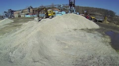 Excavator stands on pile of gravel near factory at sunny day Stock Footage