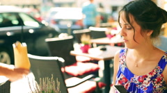 Pretty girl sitting in the street cafe and waiter bringing her cocktail Stock Footage