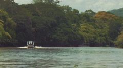 Establishing shot of a tour boat racing across a wild tropical river. Stock Footage