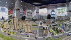 People watch scaled model of city with toy train rides Stock Footage