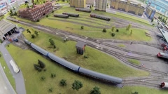 Toy train arrives to scaled model of railroad station Stock Footage