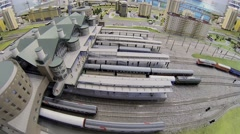 Toy train arrives to model of railway station at exhibition Stock Footage