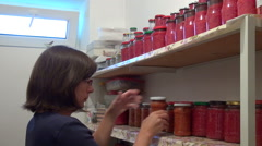 Woman stocking her pantry with goods, homemade canned food Stock Footage