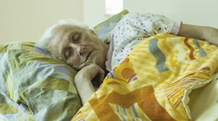 A elderly  woman Wakes Up In The Morning , awakening , old Stock Footage