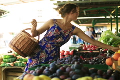 Woman putting tomatoes and peaches to the basket on the market Stock Footage
