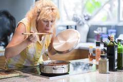 Woman tasting cooked food out of pot Stock Photos