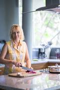 Woman preparing food in kitchen Stock Photos