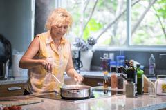 Woman heating up sauce in pan Stock Photos