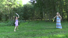 Active pregnant woman with girl play badminton game in park Stock Footage