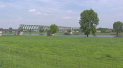 Railway bridge crossing river Meuse near Cuijk + pan floodplain landscape Stock Footage