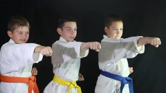 Children are trained to punch the air in a white kimono on a black background Stock Footage