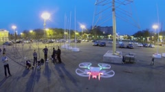 Quadrocopter flies near group of people at evening. Aerial view Stock Footage