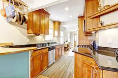 kitchen room with black granite tops and tile back splash trim - stock photo