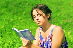 Woman sitting on the meadow and writing sad memories in the notebook Stock Footage