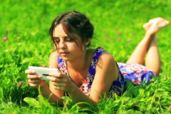 Happy girl in blue dress lying on green meadow and typing on cellphone - stock footage