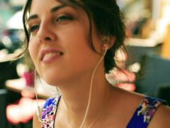 Happy woman wearing earphones and listening music in the street cafe Stock Footage