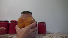 Woman hands puts jars with homemade stewed fruit on pantry shelf Stock Footage