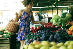 Pretty girl with basket buying red tomato on the street market Stock Footage
