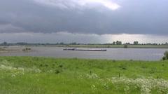 Dark cloud above river landscape,  barge passing + pan dike River Rhine Stock Footage