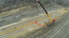 Workers build railway with crane on truck at spring day Stock Footage