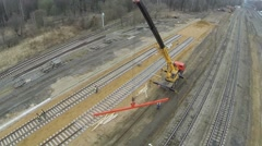 Labourers uses crane with beam at construction site of railroad Stock Footage