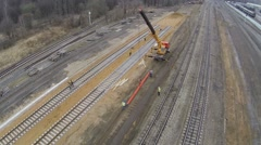 Workers uses crane with beam at building site of railway Stock Footage