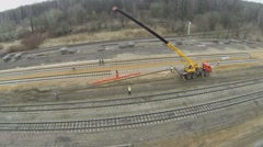 Workers uses crane with beam at building site of railroad. Stock Footage