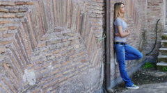Bored and lonely girl leaning against a wall: sad, sadness, thoughtful - stock footage