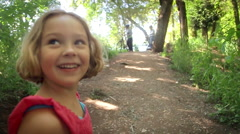 Excited Little Girl Smiles And Runs Up Nature Trail Toward Her family Stock Footage