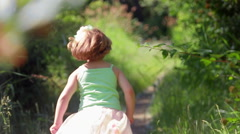 Little Girl In Dress Up Clothes, Runs Down Path, Then Stops To Pick A Flower Stock Footage