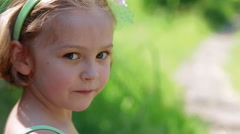 Little Girl Looks Around, Seems To Be Thinking About Something Stock Footage
