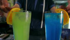 Bartender adorns two cocktails of orange slices. dolly shot. Stock Footage