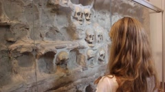 Girl Looking at Skulls Embedded in the Wall Stock Footage