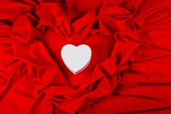 Love card with heart on a red fabric Stock Photos