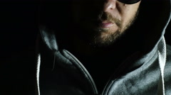 Young man in the darkness with hood and sunglasses: anger, loneliness Stock Footage